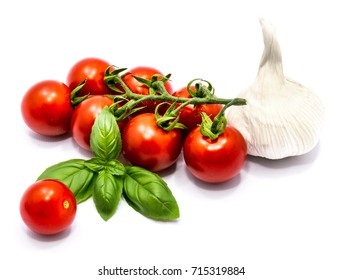 Whole red tomato cherry, one garlic and fresh basil leaves composition isolated on white background