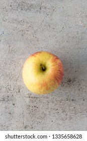 Whole red and yellow apple fruit on table concrete modern background.