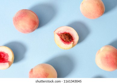 Whole ripe beautiful peaches and one split in half with putamen on a blue background