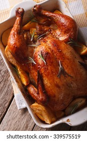 Whole roasted chicken with apples and oranges in the baking dish on a table close-up. vertical top view