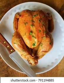 Whole roasted chicken with herb on white plate