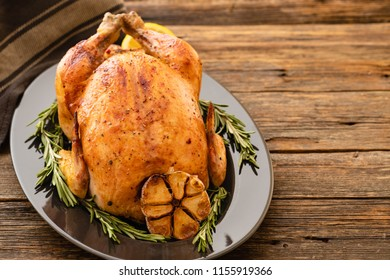Whole roasted chicken with lemon and rosemary on a black plate. Rustic style. Christmas concept. Christmas turkey. Top view.