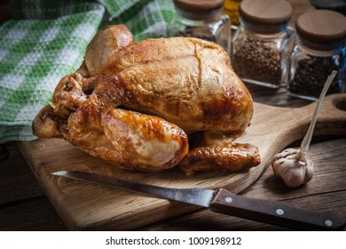Whole roasted chicken on a chopping board.