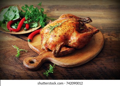 Whole roasted chicken on cutting board. Wooden rustic background