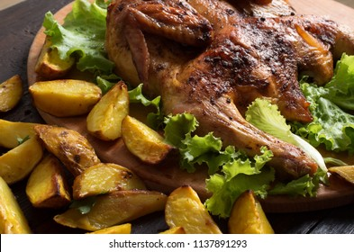 Whole roasted chicken on wooden board