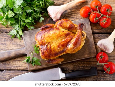 whole roasted chicken on a wooden board, top view
