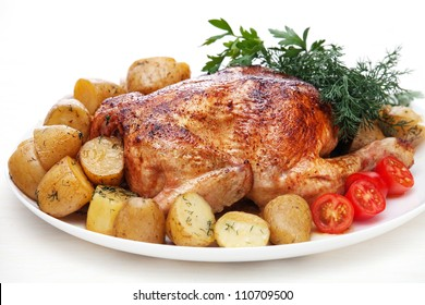 Whole roasted chicken with potatoes and herbs on white background
