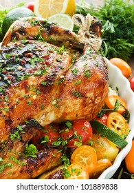 Whole roasted chicken with vegetables, herbs and fruits. Shallow dof.