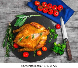 Whole Roasted Chicken with Vegetables. The ingredients for chicken baked golden cherry tomatoes, herbs spices thyme, sage, rosemary, cilantro, arugula, knife. Light wooden background. Top view.