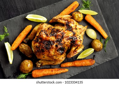 Whole roasted chicken with vegetables over black stone background. Top view