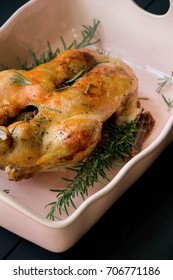 Whole roasted duck with rosemary and apple stuffing. Roasted duck in the pink porcelain pan. Christmas menu.