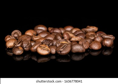 Lot of whole roasted fresh coffee bean isolated on black glass