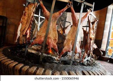 Whole Roasted lamb on a spit roast rack over a hot open Fire, cooking slowly.