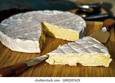 whole round of brie cheese with triangle wedge cut with cheese knife on cutting board