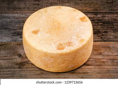 whole round cheese parmesan or pecorino on wooden background