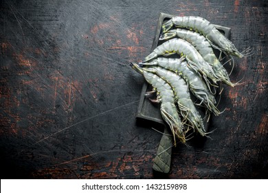 Whole shrimps raw on the cutting Board. On dark rustic background