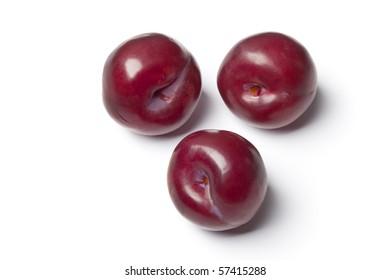 Whole single purple plums isolated on white background