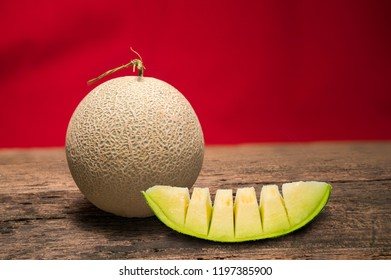 whole and slice of japanese melons on vintage wooden background, yellow melon or cantaloupe melon with seeds isolated on red background