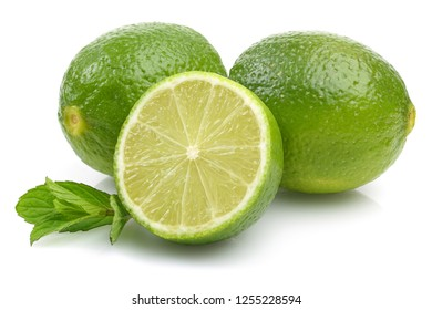 Whole and slice of lime with mint leaves isolated on white background