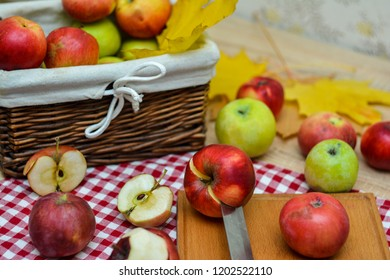 Whole and sliced apples on a red and white checkered cloth, a knife, a basket of apples.
