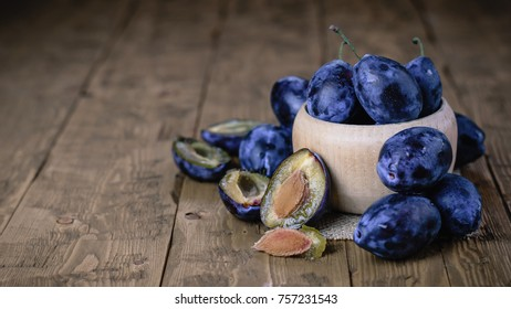 Whole and sliced blue plums in a bowl on a wooden table.