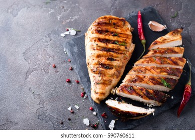 whole and sliced chicken breast with spices on a stone board, top view copy space