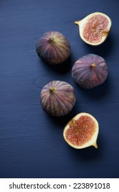 Whole and sliced figs on a dark blue wooden surface, above view