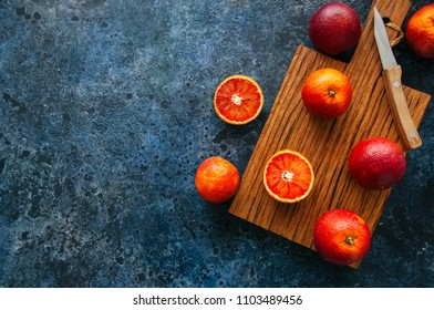 Whole and sliced fresh ripe  blood oranges on a wooden board. Top view and copy space.
