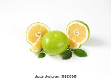 whole and sliced green grapefruit on white background