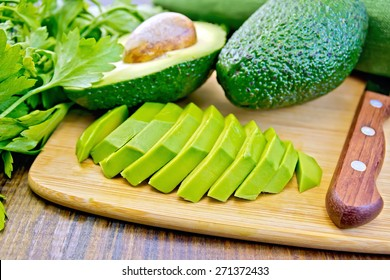 Whole, sliced and halved avocado, knife, parsley, napkin on a wooden boards background