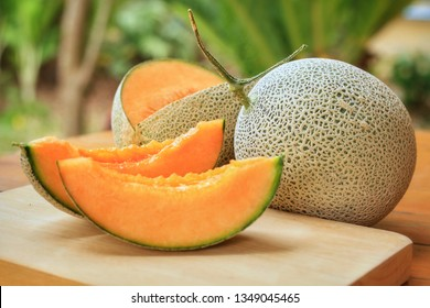 Whole and sliced of Japanese melons,honey melon or cantaloupe (Cucumis melo) on wooden table with blurred garden background.Favorite fruit in summer.Food,Fruits or healthcare concept.