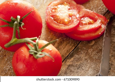 Whole and sliced juicy ripe red tomatoes on the vine on a rustic kitchen table with a knife being prepared for a salad or cooking