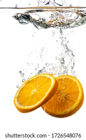 whole and sliced orange falling under water with a splash and bubbles on a white or black background