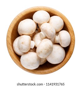 Whole small fresh white champignon mushrooms in wooden bowl isolated on white. Top view.