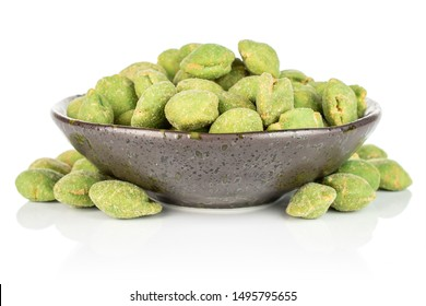 Lot of whole spicy green wasabi peanut in dark ceramic bowl isolated on white background
