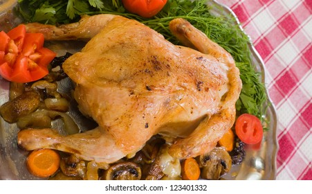 Whole stuffed chicken on tray over  checked tablecloth