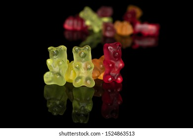 Lot of whole sweet gummy bear front focus isolated on black glass