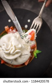Whole tied Italian cheese burrata on small wooden plate served with fresh tomatoes and basil on dark textured background. Studio shot