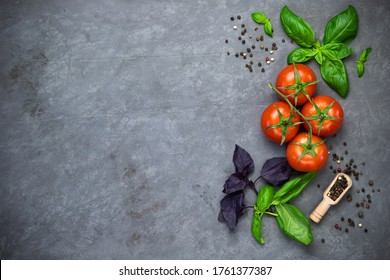 whole tomatoes on a branch and slices, basil leaves on a grey surface. ingredients: vegetables, spices, greens. background. menu, recipe.