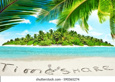 """Whole tropical island within atoll in tropical Ocean. Uninhabited and wild subtropical isle with palm trees. Inscription """"TimeShare"""" in the sand on a tropical island,  Maldives."""