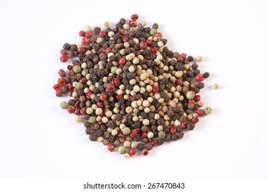 Whole uncracked multicolored peppercorns on a white background.