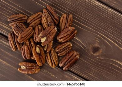 Lot of whole unshelled fresh brown pecan nut half flatlay on brown wood