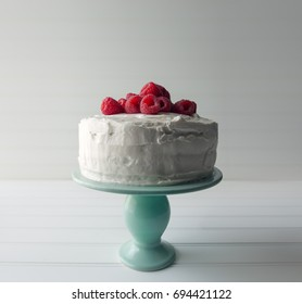 Whole vanilla frosted cake on an aqua blue cake plate with raspberry topping.