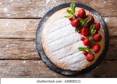 whole Victoria sandwich cake, decorated with strawberries, cranberries and mint closeup on the table. horizontal view from above