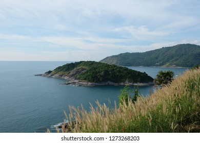 whole view of Prom thep cape island in the sea in south of Phuket Island Thailand. Blue sky and wide vast sea ocean water. little green island. Many brown reed as foreground