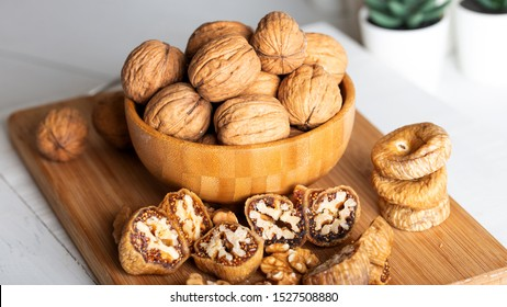 Whole walnuts in bowl. Dried figs with walnuts on wooden background.