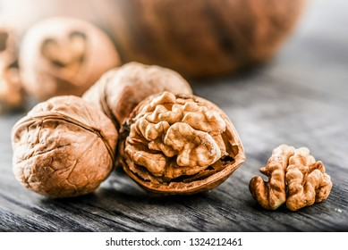 Whole walnuts on dark board, Walnut kernels in wood rustic bowl. Healthy food nuts.