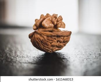 Whole walnuts on dark board.  Walnut kernels on dark background. Healthy food nuts.