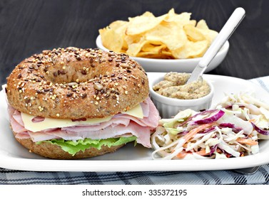 A whole wheat bagel sandwich of ham, swiss cheese and mayo with a side of spicy mustard and cole slaw salad.