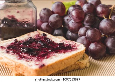 Whole wheat bread with grape jelly spread on wooden table.